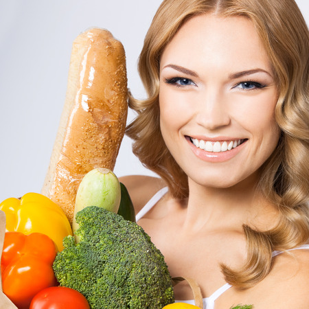 Portrait of happy smiling young beautiful woman with healthy vegetarian raw food, over gray wall photo