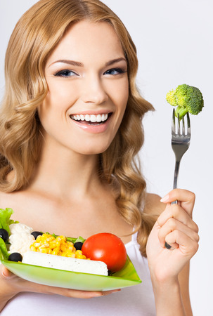 Portrait of happy smiling young beautiful woman with healthy vegetarian salad, over gray wall photo