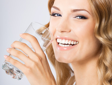 girl drinking water: Portrait of young happy smiling woman drinking water, over gray wall Stock Photo
