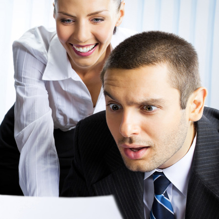 Two young happy smiling surprised businesspeople working with document or contract at office photo