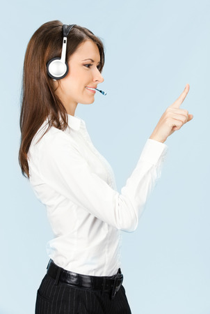 Portrait of happy smiling cheerful customer support phone operator in headset pointing at something photo