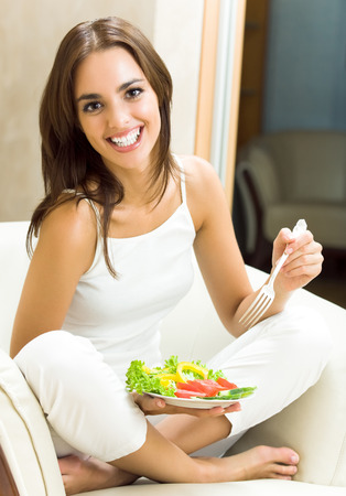 Portrait of happy smiling young woman with vegetarian vegetable salad, at home