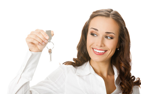 hand over: Young happy smiling business woman or real estate agent showing keys from new house, isolated over white background Stock Photo