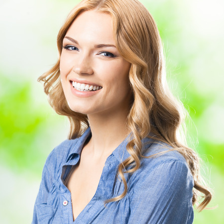 Portrait of beautiful young happy smiling blond woman with long hair, outdoors photo