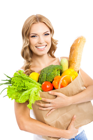 Happy smiling young beautiful woman holding grocery shopping bag with healthy vegetarian raw food, isolated over white background photo