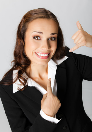 Young happy smiling business woman with call me gesture, over grey background Stock Photo