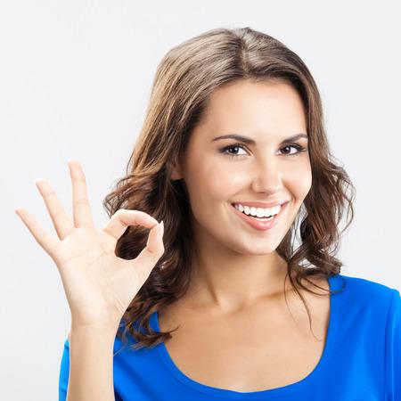Porträt der jungen fröhliche lächelnde Frau zeigt in Ordnung Geste, über grauem Hintergrund