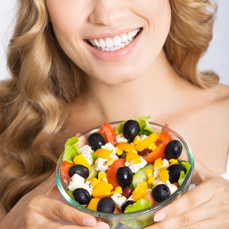 Close up photo of happy smiling young beautiful woman with healthy vegetarian salad, over gray background photo