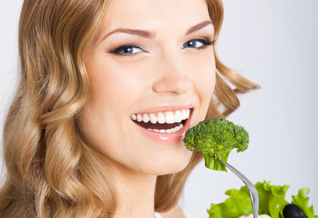 over eating: Portrait of happy smiling young beautiful woman eating broccoli, over gray background