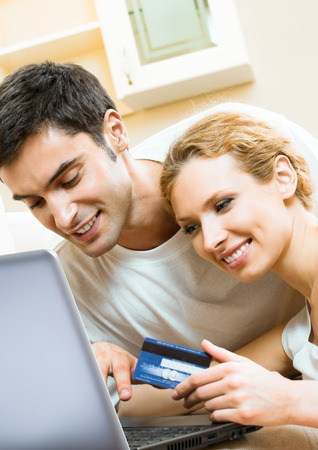 Cheerful smiling couple paying by plastic card with laptop, indoors photo