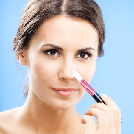 Young happy smiling woman with cosmetics brush, over blue background photo