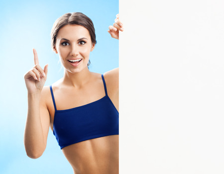 blank center: Cheerful young woman in fitness wear showing blank signboard or copyspace, over blue background Stock Photo