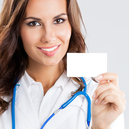 Portrait of happy smiling young female doctor showing blank business card or invitation, over grey Stock Photo - 27858363