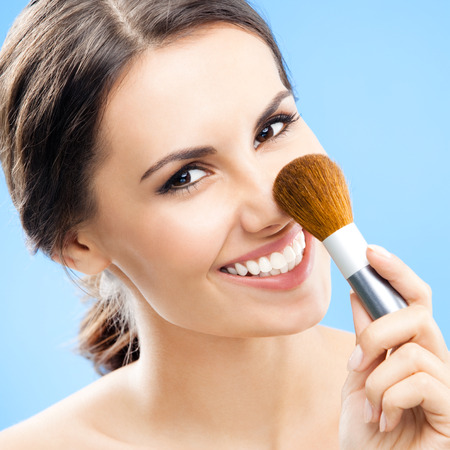 Young happy smiling woman with cosmetics brush, blue background photo