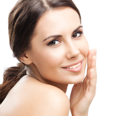 Portrait of happy smiling beautiful young woman touching skin or applying cream, isolated over white background photo