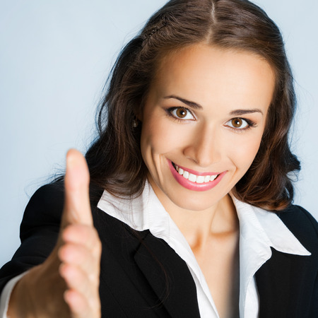 Portrait of young cheerful beautiful business woman giving hand for handshake, over blue background photo