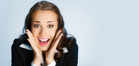 Portrait of young happy surprised business woman, over blue background photo