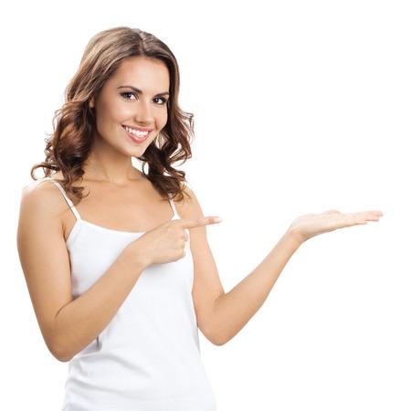 Glücklich lächelnde schöne junge Frau zeigt Exemplar oder etwas, über weißem Hintergrund Standard-Bild - 28002464