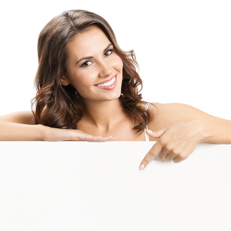 Happy smiling beautiful young woman showing blank signboard or copyspace for slogan or text, isolated over white background photo