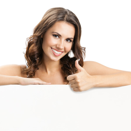 over white background: Happy smiling beautiful young woman showing blank signboard or copyspace for slogan or text, isolated over white background