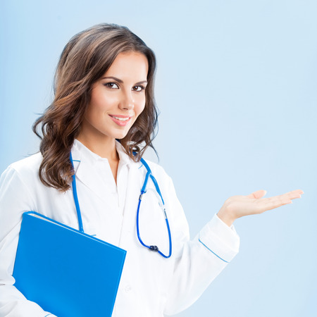 woman doctor: Portrait of young female doctor showing something or copyspase for product or sign text, with blue foder, over blue background