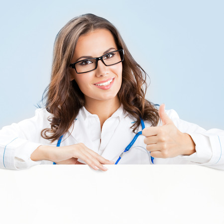 Portrait of happy smiling young female doctor showing blank signboard, over blue background photo