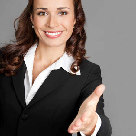 welcoming: Portrait of young cheerful beautiful business woman giving hand for handshake, over grey background