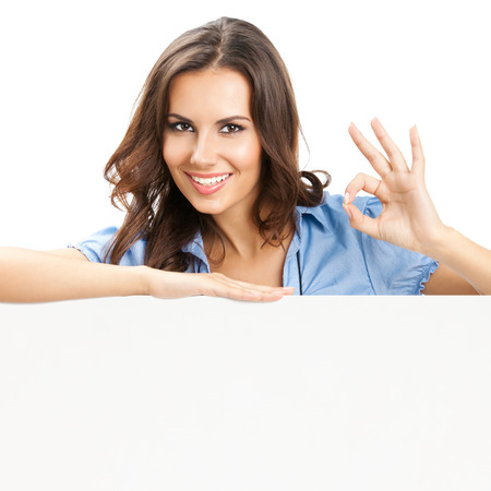Glücklich lächelnde schöne junge Frau zeigt leere Schild oder copyspace, isoliert auf weißem Hintergrund