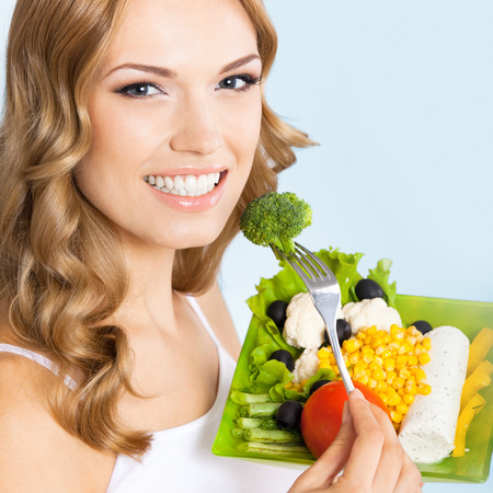 Portrait of happy smiling young beautiful woman with healthy vegetarian salad with broccoli, over blue background photo