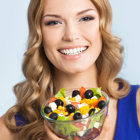 Portrait of happy smiling young beautiful woman with healthy vegetarian salad, over blue background photo