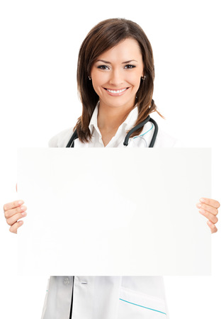 Cheerful young female doctor showing signboard with copyspace for text or design, isolated over white background photo
