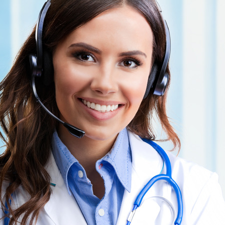 health care worker: Portrait of happy smiling young doctor in headset, at office
