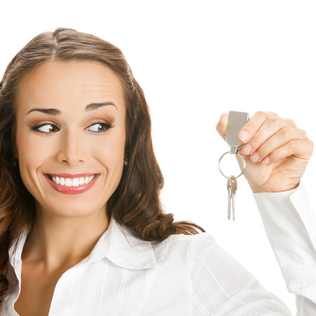 service broker: Young happy smiling business woman or real estate agent showing keys from new house, isolated over white background Stock Photo