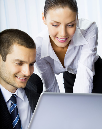 Two smiling young businesspeople working with laptop at office Stock Photo - 28365086