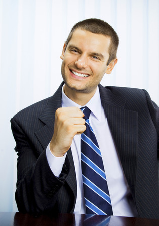 Happy successful gesturing businessman at office Stock Photo - 28365087