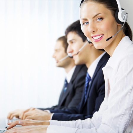 Three happy smiling young customer support phone operators at workplace Stock Photo - 28365089