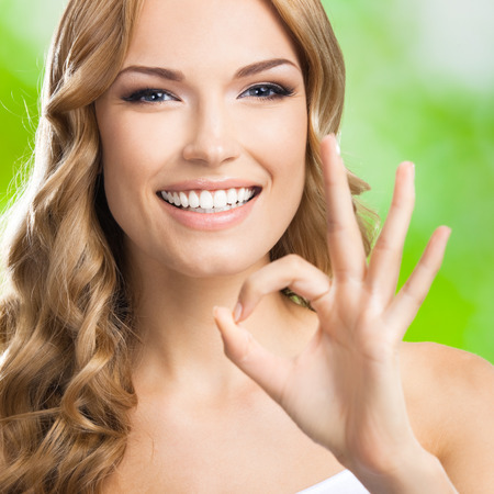 ok hand: Portrait of beautiful young happy smiling blond woman with okay gesture, outdoors Stock Photo