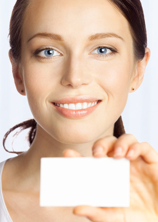 Portrait of smiling business woman giving blank business card, at office Stock Photo - 28511963