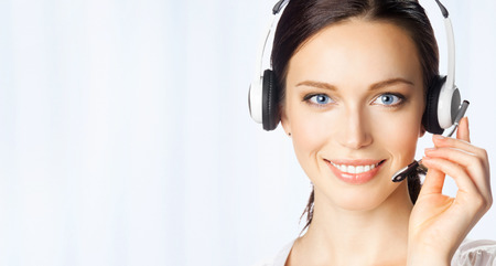 telecom: Portrait of happy smiling cheerful beautiful young support phone operator in headset, at office, with copyspace area Stock Photo