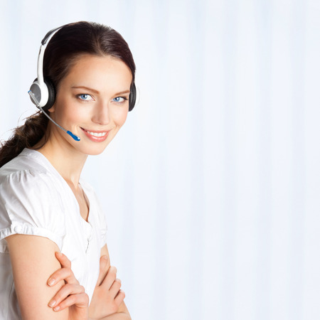 support agent: Portrait of happy smiling cheerful beautiful young support phone operator in headset, at office, with copyspace area Stock Photo
