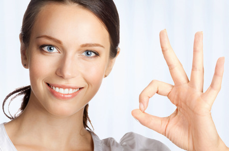 Happy smiling young beautiful business woman showing okay gesture, at office photo