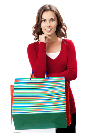 Portrait of young happy smiling woman in red casual clothing with shopping bags, isolated over white background photo