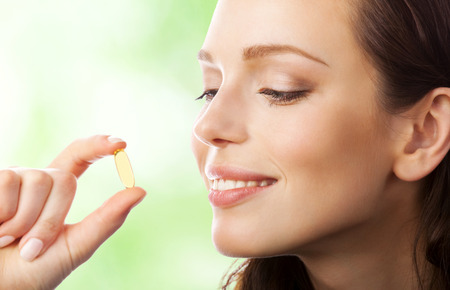 Portrait of woman with Omega 3 fish oil capsule, outdoors Stock Photo