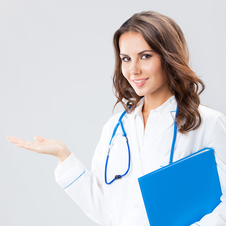Portrait of young female doctor showing something or copyspase for product or sign text, with blue foder, over grey background photo