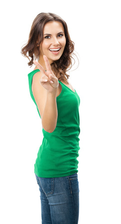 2 persons only: Happy smiling beautiful young woman showing two fingers or victory gesture, in smart green casual clothing, isolated over white background