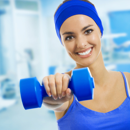 Young happy woman doing fitness exercises, at fitness club or center photo