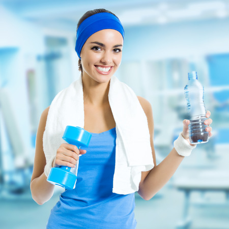 Portrait of happy smiling young woman in fitness wear with bottle of water, at fitness club or center photo