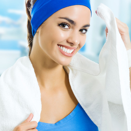 Portrait of happy smiling young woman in fitness wear with towel, at gym photo