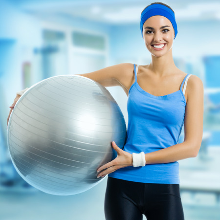 Portrait of young happy smiling woman with fitness ball, at fitness club or center photo