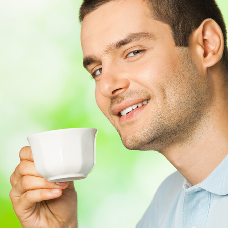Young happy smiling man with cup of coffee, outdoors photo
